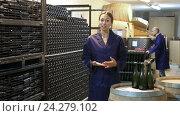 Купить «woman in uniform standing in wine processing section», видеоролик № 24279102, снято 7 сентября 2016 г. (c) Яков Филимонов / Фотобанк Лори