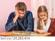 Купить «Дочка собирает картинку из пазлов, папа устало сидит рядом», фото № 24283414, снято 28 ноября 2016 г. (c) Иванов Алексей / Фотобанк Лори