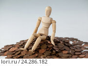 Купить «Wooden figurine sitting on heap of coins», фото № 24286182, снято 23 августа 2016 г. (c) Wavebreak Media / Фотобанк Лори