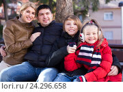 Купить «Happy family of four relaxing together», фото № 24296658, снято 22 ноября 2018 г. (c) Яков Филимонов / Фотобанк Лори