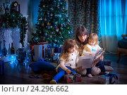 Купить «Мать читает книгу дочерям в канун Рождества», фото № 24296662, снято 30 ноября 2016 г. (c) Julia Shepeleva / Фотобанк Лори