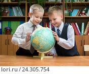 """Купить «Два мальчика-первоклассника изучают глобус на уроке """"Окружающего мира""""», эксклюзивное фото № 24305754, снято 3 ноября 2015 г. (c) Вячеслав Палес / Фотобанк Лори"""