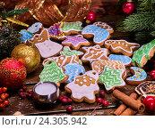 Купить «Christmas gingerbread cookies on woden table and candels.», фото № 24305942, снято 30 ноября 2016 г. (c) Gennadiy Poznyakov / Фотобанк Лори