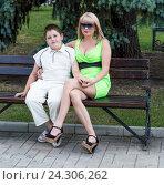 Красивая женщина в зеленом платье с ребенком на скамейке. Стоковое фото, фотограф Serghei Poberejniuc / Фотобанк Лори