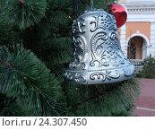 Купить «Серебристый колокольчик на искусственной новогодней елке на городской площади», фото № 24307450, снято 25 декабря 2015 г. (c) DiS / Фотобанк Лори