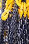 Черная стальная цепь и желтые грузовые крюки, фото № 24318310, снято 28 ноября 2016 г. (c) Андрей Радченко / Фотобанк Лори