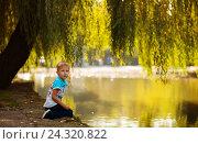 Мальчик сидит на берегу пруда (2016 год). Редакционное фото, фотограф Елена Ганненко / Фотобанк Лори