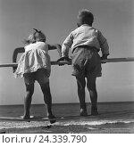 Купить «Zwei kleine Kinder turnen an einem Gelände am Strand der Ostsee in Ostpreußen, Deutschland 1930er Jahre. Two little children playing at a railing on the...», фото № 24339790, снято 23 июля 2018 г. (c) mauritius images / Фотобанк Лори