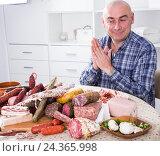 Купить «Мужчина сидит за столом перед разнообразными колбасными изделиями и потирает руки», фото № 24365998, снято 17 ноября 2016 г. (c) Татьяна Яцевич / Фотобанк Лори