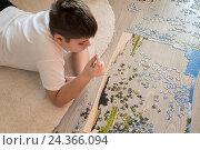 Купить «Teen boy collects a puzzle lying on carpet», фото № 24366094, снято 31 октября 2015 г. (c) Володина Ольга / Фотобанк Лори