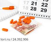 Купить «Оранжевые таблетки, деньги и календарь», фото № 24392906, снято 6 декабря 2016 г. (c) Наталья Осипова / Фотобанк Лори