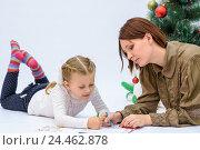 Купить «Мама с маленькой дочкой пишут письмо Деду Морозу рядом с елкой», фото № 24462878, снято 9 декабря 2016 г. (c) Гетманец Инна / Фотобанк Лори