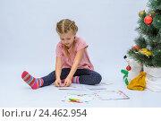 Купить «Маленькая девочка клеит марку на письмо Деду Морозу на елку», фото № 24462954, снято 9 декабря 2016 г. (c) Гетманец Инна / Фотобанк Лори