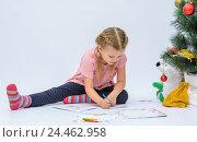 Купить «Маленькая девочка в новогодней шапочке пишет письмо Деду Морозу рядом с елкой», фото № 24462958, снято 9 декабря 2016 г. (c) Гетманец Инна / Фотобанк Лори