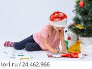 Купить «Маленькая девочка в новогодней шапочке пишет письмо Деду Морозу рядом с елкой на белом фоне», фото № 24462966, снято 9 декабря 2016 г. (c) Гетманец Инна / Фотобанк Лори