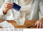 woman pouring medication into cup of water. Стоковое фото, фотограф Syda Productions / Фотобанк Лори