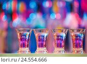 Купить «Burning drinks in shot glasses on a bar counter», фото № 24554666, снято 26 марта 2016 г. (c) Сергей Новиков / Фотобанк Лори