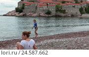 Купить «Мама с ребенком отдыхают на берегу моря перед островом Свети Стефан, Черногория», видеоролик № 24587662, снято 25 октября 2016 г. (c) Кекяляйнен Андрей / Фотобанк Лори