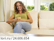 Купить «Woman, sit young, couch, view camera, smile, tea, drink, model released, people, blond, curls, long-haired, leant back, recreation, rest, take it easy...», фото № 24606654, снято 8 января 2009 г. (c) mauritius images / Фотобанк Лори