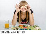 Купить «Молодая девушка приложила ролл к глазам и с улыбкой смотрит в кадр», фото № 24645110, снято 29 сентября 2013 г. (c) Иванов Алексей / Фотобанк Лори