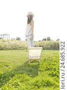 Купить «young woman stands beside chair on a meadow,», фото № 24685922, снято 21 июля 2018 г. (c) mauritius images / Фотобанк Лори