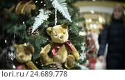 Купить «Plush bear balls and fir cone. New Year's and abstract blurred shopping mall background with Christmas tree decorations.», видеоролик № 24689778, снято 11 декабря 2016 г. (c) vvo1tv / Фотобанк Лори