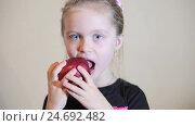 Девочка в черной футболке есть красное яблоко. Стоковое видео, видеограф Иван Карпов / Фотобанк Лори