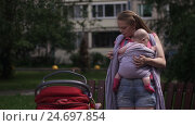 Young mother put on baby sling holding little child. Baby carriage. Summer day. Стоковое видео, видеограф Александр Багно / Фотобанк Лори