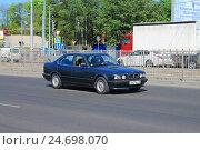 Купить «Черный автомобиль БМВ 5 серии на дороге в солнечный день», фото № 24698070, снято 11 мая 2016 г. (c) Михаил Рудницкий / Фотобанк Лори