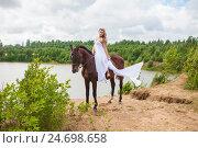 Купить «Девушка в белом развивающимся платье верхом на лошади», эксклюзивное фото № 24698658, снято 16 июля 2016 г. (c) Литвяк Игорь / Фотобанк Лори