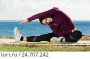 Купить «Cheerful girl exercising on exercise mat», фото № 24707242, снято 26 мая 2019 г. (c) Яков Филимонов / Фотобанк Лори