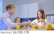 Купить «Eating family in kitchen», видеоролик № 24709178, снято 18 января 2020 г. (c) Raev Denis / Фотобанк Лори