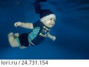 Купить «Маленький мальчик в новогоднем колпаке плывет под водой в бассейне», фото № 24731154, снято 15 декабря 2016 г. (c) Некрасов Андрей / Фотобанк Лори