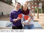 Счастливая пожилая пара с теннисными ракетками в руках стоит около стола в городском парке. Стоковое фото, фотограф Татьяна Яцевич / Фотобанк Лори