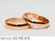 Купить «Два золотых обручальных кольца на светлом фоне», эксклюзивное фото № 24745418, снято 12 ноября 2016 г. (c) Игорь Низов / Фотобанк Лори
