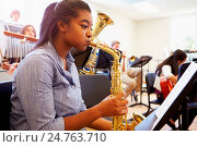 Купить «Female Pupil Playing Saxophone In High School Orchestra», фото № 24763710, снято 12 апреля 2014 г. (c) easy Fotostock / Фотобанк Лори