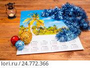 Купить «Сувенирный календарь с тропическим пейзажем, елочные шары и мишура на деревянном столе», фото № 24772366, снято 25 декабря 2016 г. (c) Сергей Дубров / Фотобанк Лори