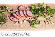 Нарезанные ломтики колбасы, зелень и специи на деревянной разделочной доске. Стоковое фото, фотограф Igor Sirbu / Фотобанк Лори
