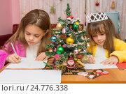 Купить «Две девочки пишут письмо деду морозу, фокусировка на елочке посередине», фото № 24776338, снято 25 декабря 2016 г. (c) Иванов Алексей / Фотобанк Лори