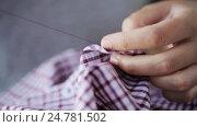 Купить «woman with needle stitching on button to shirt», видеоролик № 24781502, снято 3 октября 2016 г. (c) Syda Productions / Фотобанк Лори