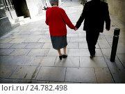 Dos personas mayores, hombre y mujer vistos de espaldas cojidos de la mano andando por una calle de Barcelona, Cataluña, España, Europa. Стоковое фото, фотограф Lluís Real / age Fotostock / Фотобанк Лори