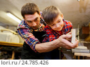 Купить «father and little son with wood plank at workshop», фото № 24785426, снято 14 мая 2016 г. (c) Syda Productions / Фотобанк Лори