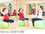 Купить «pregnant woman with instructor doing fitness ball exercise», фото № 24817450, снято 3 ноября 2015 г. (c) Дмитрий Калиновский / Фотобанк Лори