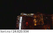 Купить «SLOW: A cola drink in glass with ice on a black background», видеоролик № 24820934, снято 16 апреля 2016 г. (c) Евгений Киблер / Фотобанк Лори