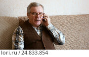 Old man sitting on the couch at home talking on smartphone. Стоковое видео, видеограф Сергей Кальсин / Фотобанк Лори