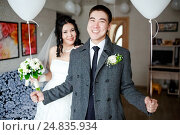 Купить «Happy groom with balloons in his hands, indoors at wedding day, the bride in the background», фото № 24835934, снято 20 февраля 2016 г. (c) Евгений Майнагашев / Фотобанк Лори