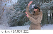 Купить «Woman putting on and using virtual reality glasses in winter forest», видеоролик № 24837222, снято 6 января 2017 г. (c) Aleksey Popov / Фотобанк Лори