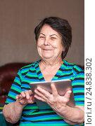 Счастливая пожилая женщина в руках держит планшет и смотрит в кадр, фото № 24838302, снято 6 января 2017 г. (c) Эдуард Паравян / Фотобанк Лори