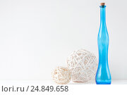 Купить «Minimal elegant composition with rattan balls and blue bottle», фото № 24849658, снято 29 декабря 2016 г. (c) Екатерина Рыбина / Фотобанк Лори