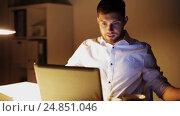 Купить «man with laptop and papers working at night office», видеоролик № 24851046, снято 4 декабря 2016 г. (c) Syda Productions / Фотобанк Лори
